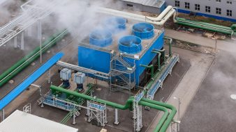 Industrial blue cooling tower at a chemical plant.