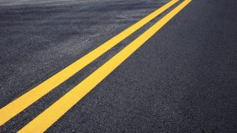Traffic line of yellow on street with texture background.
